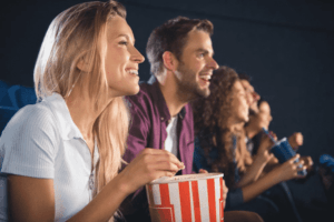 man and woman eating popcorn in movie theater