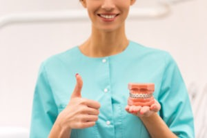 dentist holding a dental model with braces and giving thumbs up