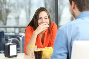 woman covering teeth