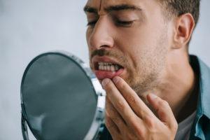 man looking at teeth in mirror